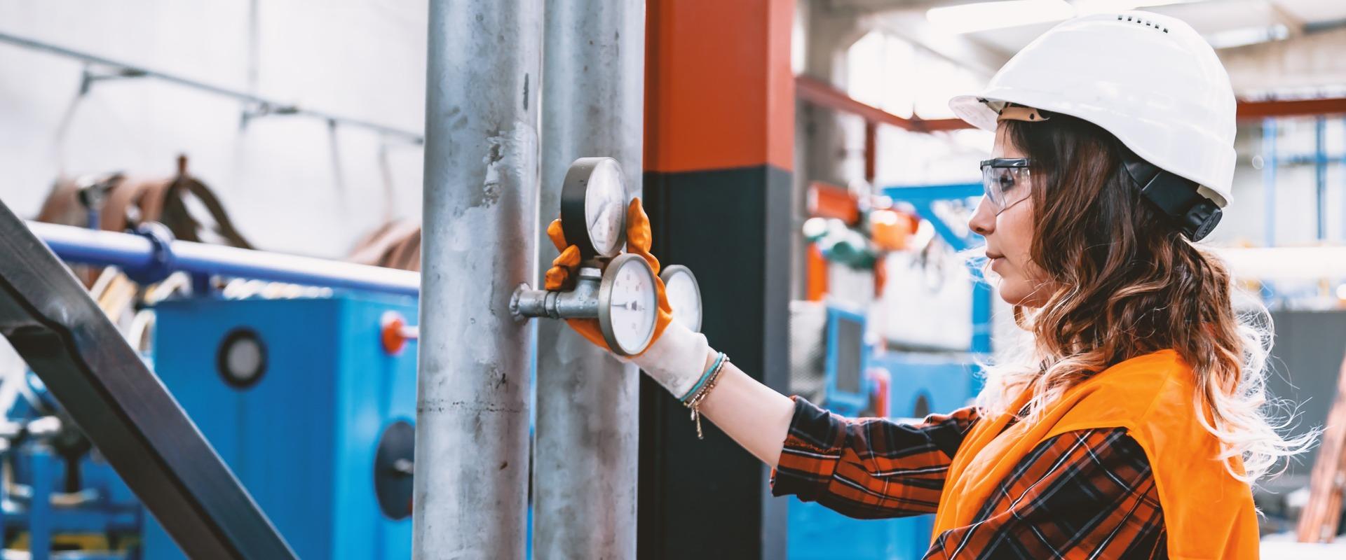 Women performing boiler maintenance check on valves
